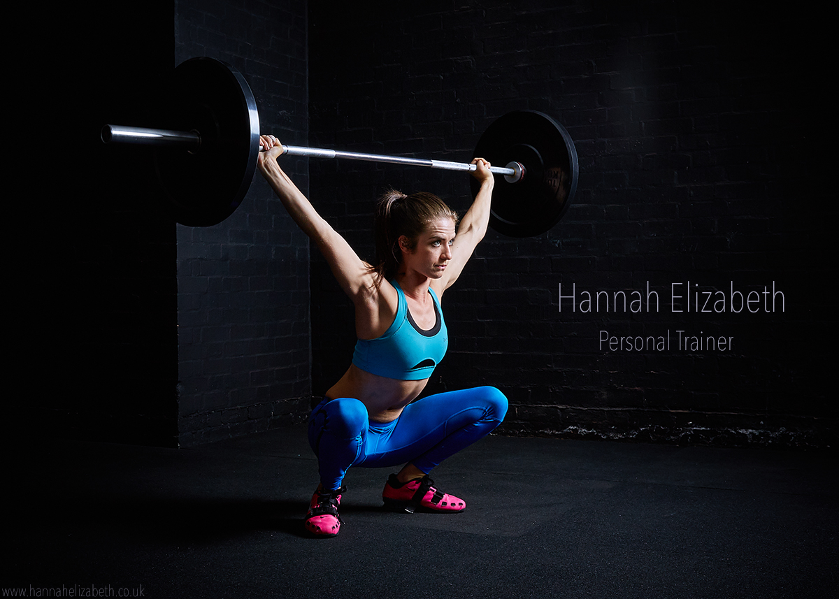 Image of Hannah performing an overhead squat with a barbell. The background and floor is black, she has dark brown hair and is wearing a turquoise bright blue leggings, fluorescent pink weightlifting shoes