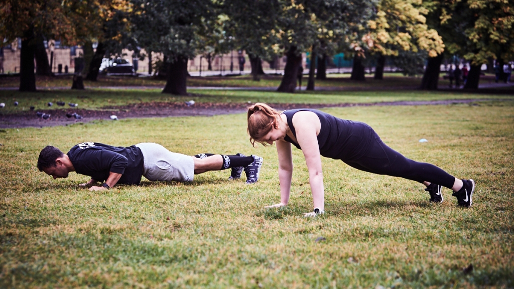 Image of a man and a woman outside during a workout in the park. They are  both dressed in black workout clothes, the man is in the bottom position of a push up and the woman is holding a plank. They are in the grass with trees visible in the distance.