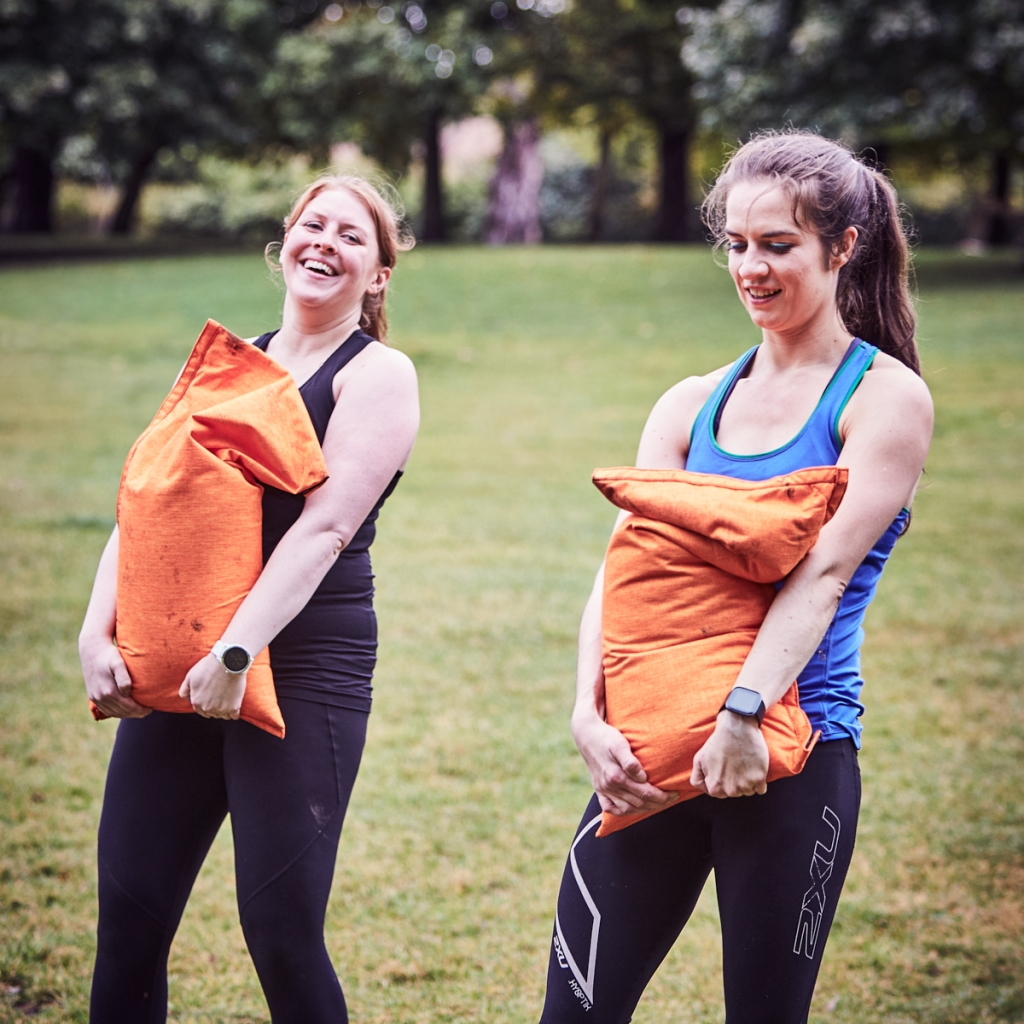 Image of two women, Hannah and Becky. They are outside, holding heavy orange sandbags during a workout. They are both smiling