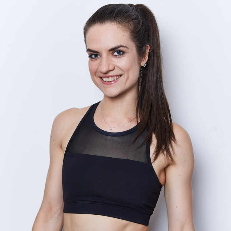Image of Hannah. She is smiling and looking into the camera. She has dark brown hair and wears a small silver star necklace, set over a black sports bra.